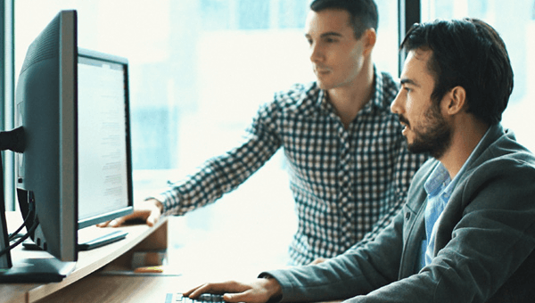 Two people working together at computer monitors.