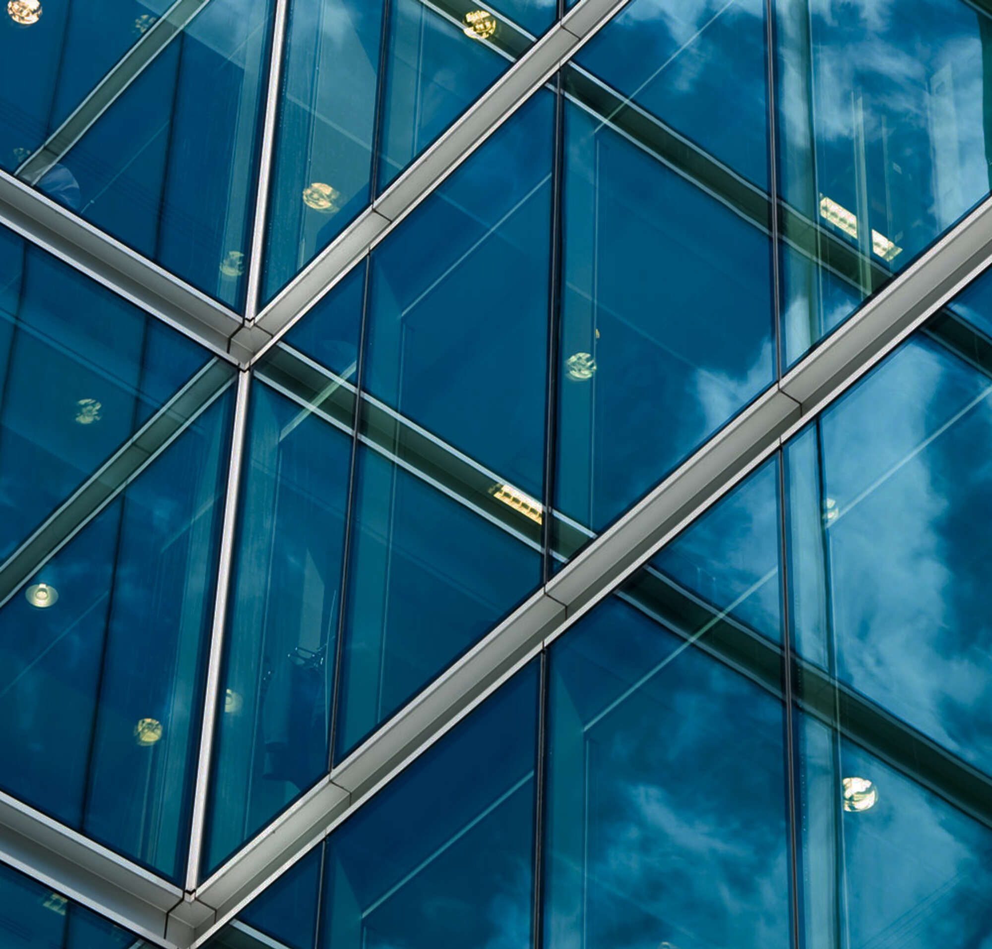 Reflective windows on a building reflecting lights, a blue sky with clouds, and other windows.