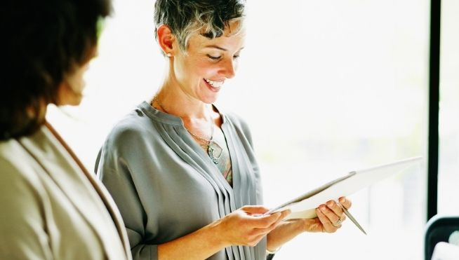 Smiling business woman looks at notepad